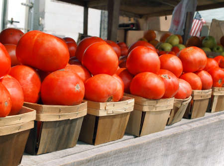 lycopene: A row of vibrant red, juicy, farm fresh tomatoes for sale in little wooden baskets at a local farmers market. Stock Photo
