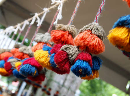 multilayered: A row of bright, colorful, multi-layered fancy tassels hanging from a rope decorate an outdoor festival booth.