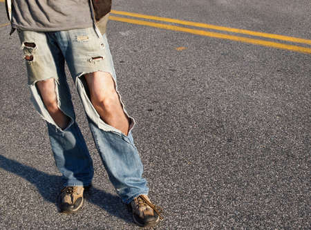 causal: A young man, from the waist down,  in a causal t-shirt and ripped jeans with hair legs exposed stands in the road. Stock Photo