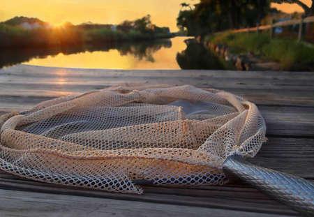 A pole style crab net lies on a dock over a river at sunset.