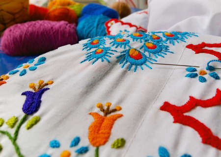 Closeup of a beautiful floral embroidery project with multiple colors of embroidery thread and a needle on white cloth.