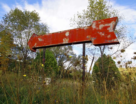 decomposition: An old red arrow signs stands overgrown with weeds, rusting away on an autumn afternoon.