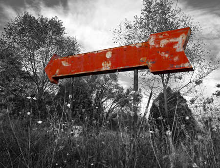 A red vintage arrow sign in a desaturated black and white landscape of weeds, trees, and sky. Stock Photo