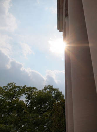 A sunburst from high in the sky beams through the columns of a Greek or Roman style building with tree tops in the background. Stock Photo