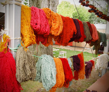Skeins of freshly dyed spun wool fibers in a variety of beautiful colors displayed hanging on a line outdoors.