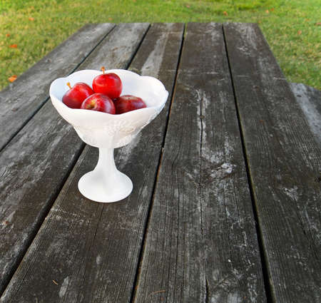 Fresh red apples in a vintage milk glass compote on a picnic table.