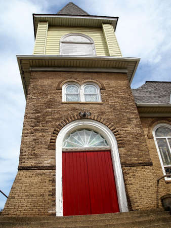 Vibrant red doors and round top stained glass windows in the brick facade of an old church.