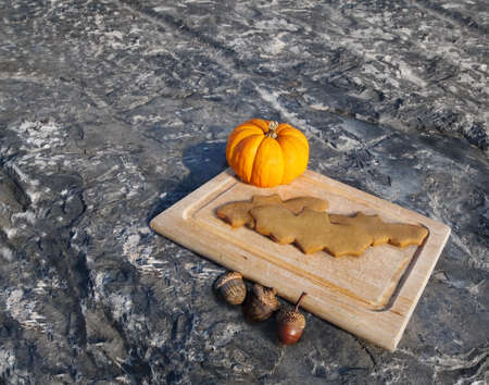 A serving of bat shaped gingerbread cookies on a cutting board with a miniature pumpkin and some acorns. Stock Photo