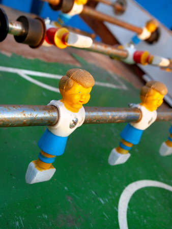 Closeup on a plastic foosball player on a control stick on a rusty old game table.