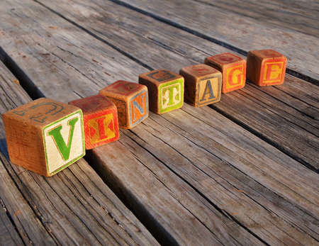 The word VINTAGE is spelled out in old, fading, antique alphabet blocks, with copy space. Stock Photo