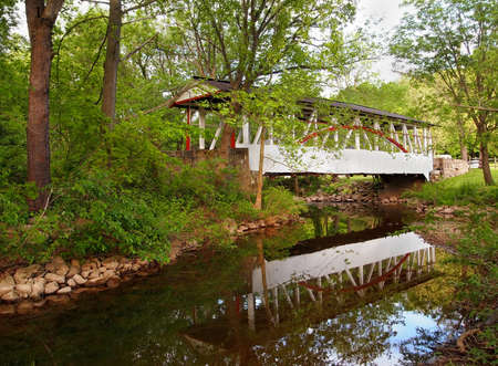 A beautiful example of a traditional wooden covered bridge, crossing Dunnings Creek and reflecting on the water, in Bedford County, Pennsylvania.