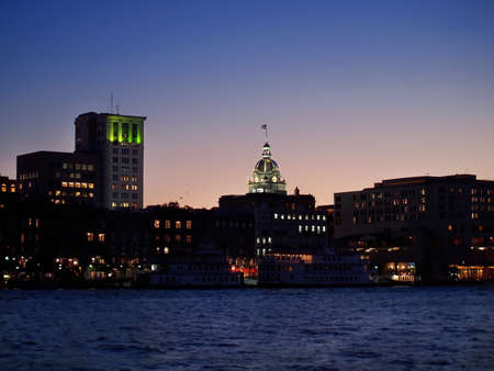 The gold-leafed dome of City Hall, in Savannah, GA viewed from across the Savannah River,  just after sunset. Stock Photo