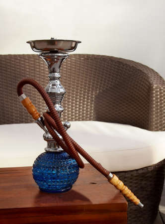 A large, blue, luxury glass hookah sits on a table in the sunshine at an outdoor hookah lounge with a rattan couch. Stock Photo
