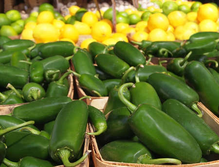 Baskets of fresh, hot, green jalapeno peppers for sale at a  local farmers market with citrus fruits in the background.