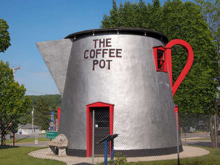 BEDFORD, PENNSYLVANIA - MAY 24, 2015: The Coffee Pot, an 18 ft tall coffee pot shaped building originally built in the 1920s, was restored in the early 2000s and still stands by the side of the road on Lincoln Highway in Bedford, PA.