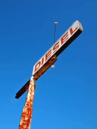 A vintage Diesel fuel sign on a tall rusting pole far above the highway against a brilliant blue sky.