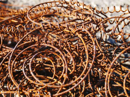 A pile of rusty, discarded, old couch springs on the ground in an empty lot.