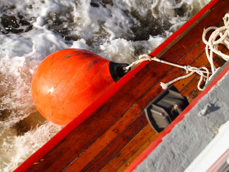 A bright orange mooring buoy hangs along the side of a ferry boat, as it moves through the water.