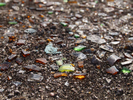 Jagged pieces of green, amber, brown, and clear broken glass on the ground with dirt in the sunlight.