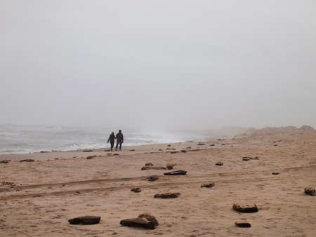 A couple walks hand in hand into the distance on a foggy beach by the waters edge.