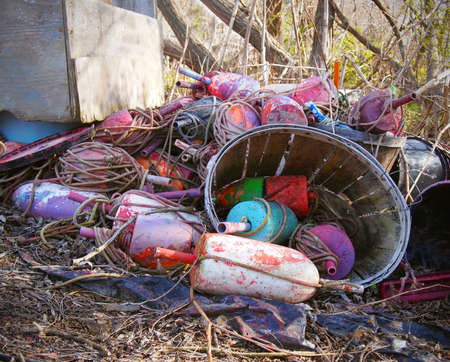 A pile of old buoys and tangled ropes with a bushel in the sticks. Stock Photo