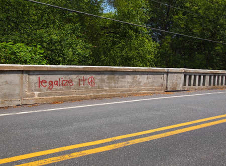 The phrase legalize it and a peace sign are spray-painted in red on a concrete jersey wall along the side of a country road with green trees and power lines in the background.