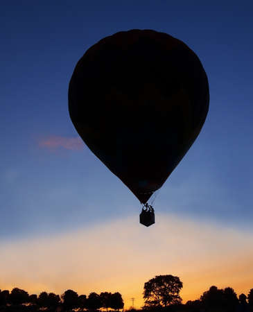 Silhouette of a hot air balloon, trees, power lines, and distant spectators at sunset in the countryside.
