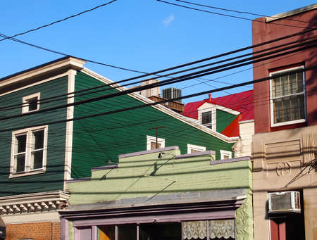 Background image of colorful vintage second story architecture, roof lines and rooftops, power lines, and blue sky.