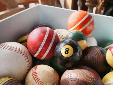 An old eightball in wooden bin full of vintage game balls, including pool, croquet, and baseball.