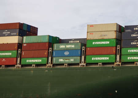 SAVANNAH, GEORGIA - FEBRUARY 22, 2020: Large shipping containers from many different shipping companies are stacked on a cargo ship leaving port, amid a strained climate of delayed and reduced shipping resulting from a virus outbreak in China. Editorial