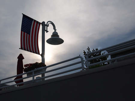 An American flag over a sundeck balcony at sunset on a quiet summer evening in a beach town.