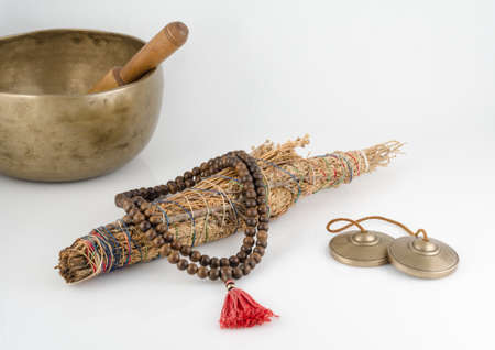 smudge: Singing Bowl, Smudge Stick, Prayer Beads and Meditation Bells.