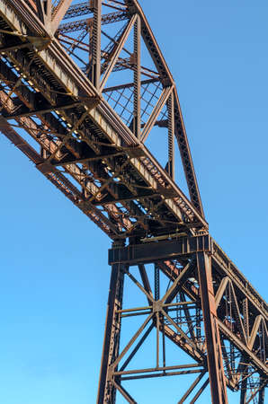 steel girder: Section of Rusty Steel Girder Railroad Bridge in Bright Daylight with Clear Blue Sky Background.