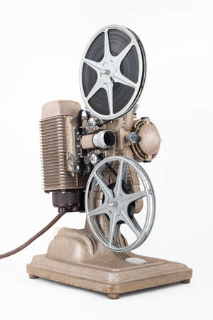 angled view: Angled view of Vintage 8 mm Movie Projector with Film Reels. Film is threaded through Projector.