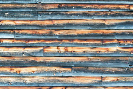 overlapped: Weathered Barn Wall with Overlapped Gray and Brown Wood Siding in Rough Condition. Stock Photo