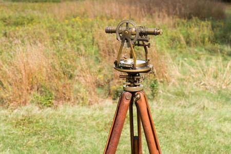 teodolito: Cierre de Nivel de Tr�nsito de la vendimia del top�grafo, teodolito tr�pode de madera en un campo.