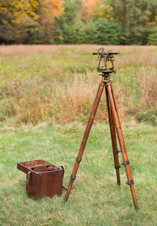 surveying: Vintage Brass Surveying Level Transit, Theodolite with Compass and natural aged Brass Patina, on a  wooden Tripod with Storage Case in a field. Stock Photo