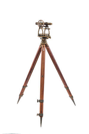 tacheometer: Vintage Surveyors Level Transit, Theodolite with aged Brass Patina  on a Wooden Tripod, focus stacked and isolated on white background.