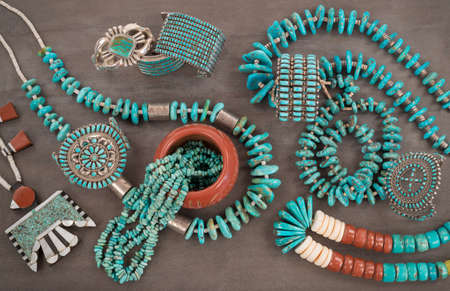 native american art: A collection of Vintage Native American Jewelry made of turquoise, silver, pipe stone and Heishe beads. A Santo Domingo Depression Era Necklace, and Turquoise Nugget necklaces with silver beads, and Zuni and Navajo Cuff Bracelets, on a Grey Slate Back