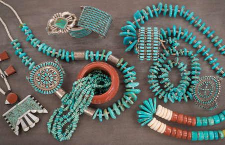 """Een verzameling van vintage Inheemse Amerikaanse sieraden gemaakt van turkoois, zilver, pijp steen en Heishe kralen. A Santo Domingo Depressie Era Ketting en Turkoois """"Nugget"""" kettingen met zilveren kralen en Zuni en de Navajo """"manchet"""" armbanden, op een grijze Slate Terug"""