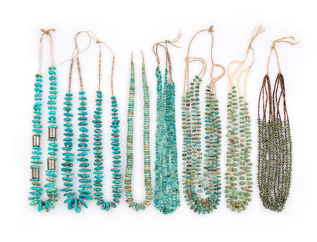 azul turqueza: Una colección de la turquesa del vintage del nativo americano collares con perlas de plata y la tortuga Cuentas Heishe de Shell que se encadenan en el catgut, sobre un fondo blanco.