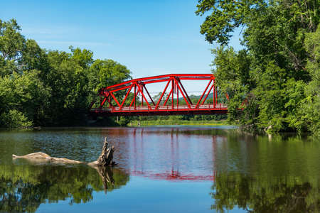 retreats: Red Bridge in bright daylight on Route 32 over the Wallkill River near Rifton in the Catskills of Upstate New York. Selective focus on the bridge. Selective focus on bridge. Stock Photo