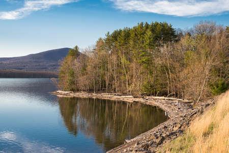 Costa del Embalse de Ashokan tomada durante la hora dorada. El Ashokan, que se encuentra en las montañas Catskill del Valle de Hudson en Nueva York, es parte del sistema de suministro de agua para Nueva York. Árboles caídos recogen a lo largo de la orilla. El embalse es un Foto de archivo