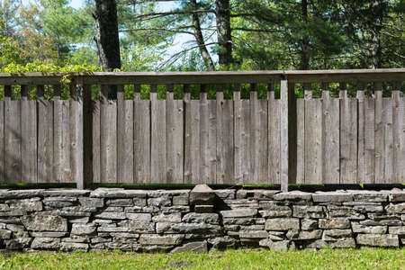 Section of Stacked Stone Wall with Grey Distressed Wood Fence in Country Setting . Grass in foreground and Trees in Background.