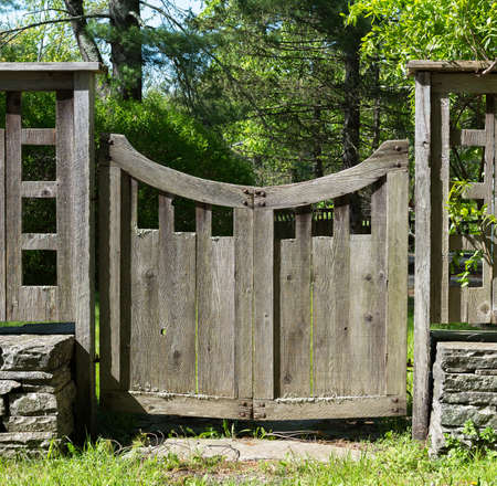wood grass: Distressed Grey Wood Gate with a Curved Top in Country Setting,  with Lichens  and Stacked Stone, Grass and Trees.