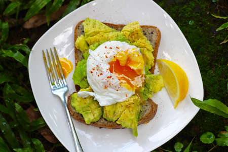 Early morning breakfast in Chiang Mai Thailand with a natural energy power supply made up with poached eggs and avocado on toast. Super yummy and healthy food that heals the soul and fuels the body. Фото со стока