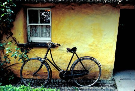 thatched roof: Old Irish Cottage and Bike leaning against yellow wall