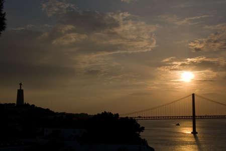 rei: Bridge 25 de Abril over Tagus river and Cristo Rei in LisbonAlmada at sunset Stock Photo