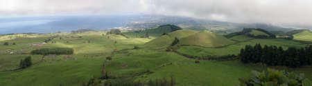 Azores, panorama of typical green pastures under a sky of clouds Stock Photo