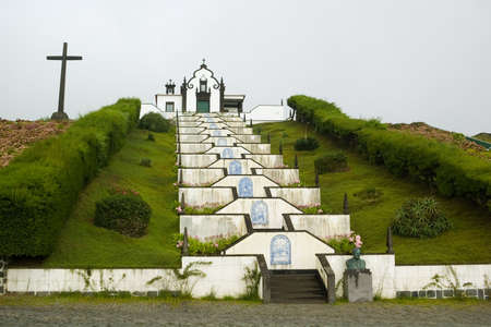 Chapel, stairs and cross of Senhora dos Milagres over Vila Franca do Campo under a sky of clouds. Azores, Portugal